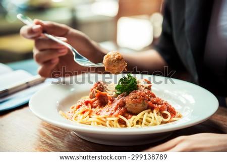 close up of woman eating spaghetti meatball - stock photo