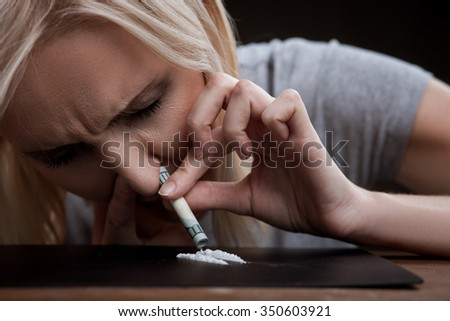Close up of woman enhancing cocaine into her nose. She is sitting and closed her eyes with depression - stock photo