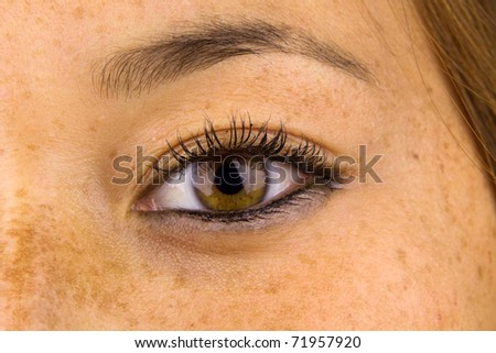Close up of woman eye and surrounding skin showing sun damage, commonly known as freckles. - stock photo