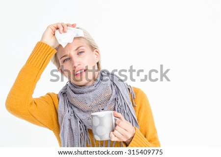 Close up of woman feeling her forehead and drinking from a cup - stock photo