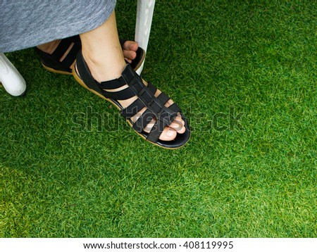 Close up of woman foot stay on Artificial Grass Field Top View.