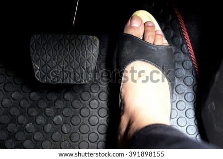 Close up of woman foot with black leather shoe on accelerator pedal in the car. Focus on black leather shoe. - stock photo