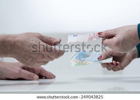 Close-up of woman giving the money to her husband - stock photo