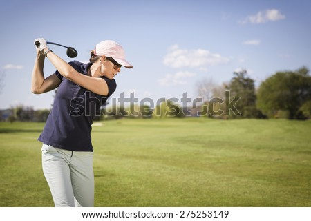 Close up of woman golf player swinging golf club, with empty copyspace. - stock photo