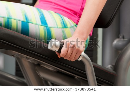 Close-up of woman hand holding a handle while sitting on leg workout machine