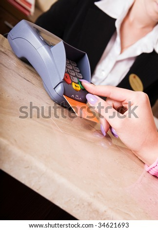 Close-up of woman hand holding credit card in payment terminal - stock photo