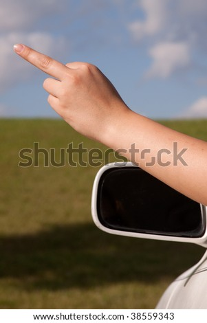 Close up of woman hand sticking out of car window with middle finger up - stock photo