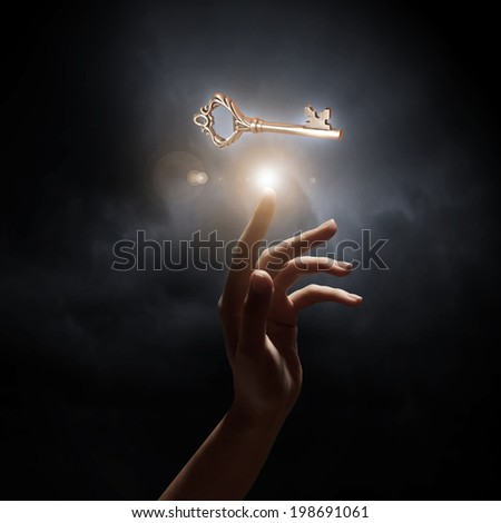 Close up of woman hand touching golden key - stock photo