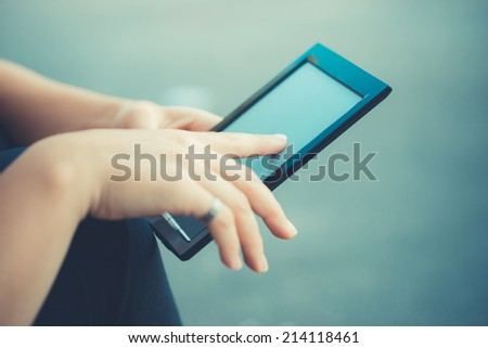 close up of woman hand using technological tablet device outdoor