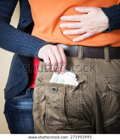 Close up of woman hands embracing man and stealing taking out money out of his pocket. Woman stealing currency. Theft concept. - stock photo