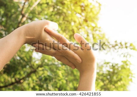 Close up of woman hands exercising in sunlight. Deep breath fresh air in the park.