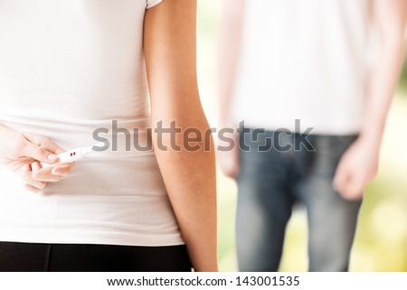 close up of woman hands hiding pregnancy test from man - stock photo