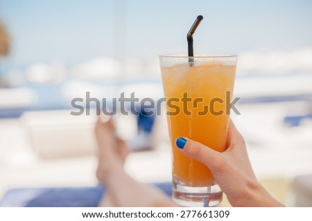 Close Up Of Woman Hands Holding Fruit Cocktail At The Beach - stock photo