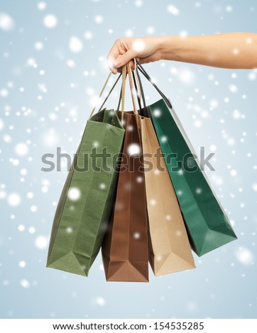 close up of woman hands holding shopping bags - stock photo
