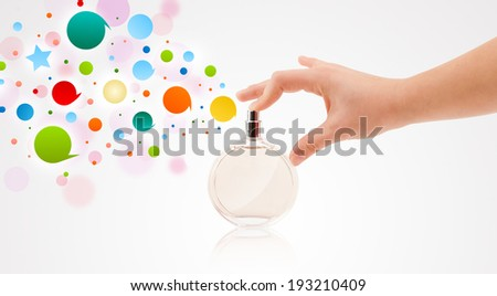 close up of woman hands spraying colorful bubbles from beautiful perfume bottle - stock photo