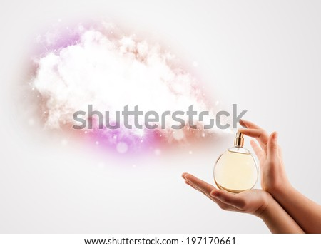 close up of woman hands spraying colorful cloud from beautiful perfume bottle - stock photo