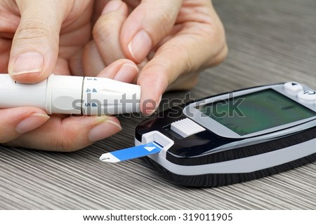 Close-up Of Woman Hands Testing High Blood Sugar With Glucometer, Blood glucose meter, The blood sugar value is measured on a finger, Syringe pen with insulin and glucometer, Blood glucose test. - stock photo