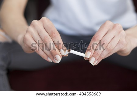 Close up of woman hands with broken cigarette. Stop smoking