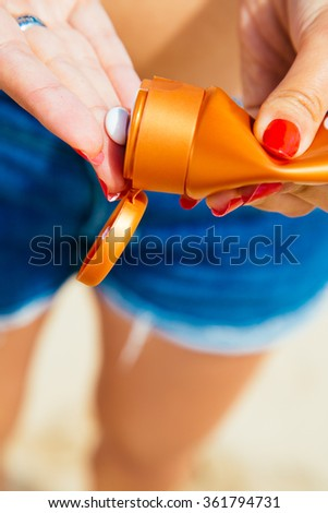Close up of woman hands with nail polished putting sunscreen lotion from a bottle - stock photo