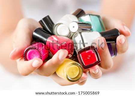Close up of woman hands with nail polishes of different colors - stock photo