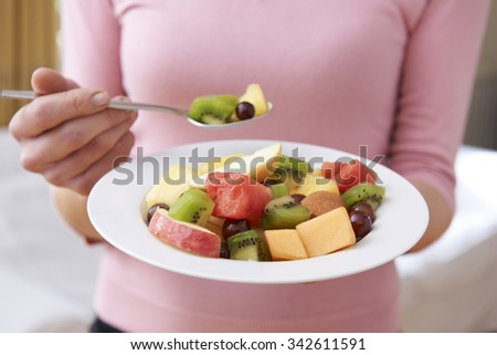 Close Up Of Woman Holding Bowl Of Fresh Fruit - stock photo