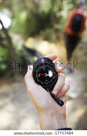 Close-up of woman holding compass on hiking trip in Varigotti, Liguria, Italy