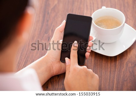 Close-up Of Woman Holding Mobile Phone In Front Of Coffee Cup - stock photo