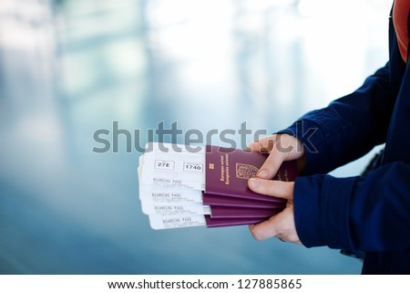 Close up of woman holding passports and boarding passport at airport - stock photo