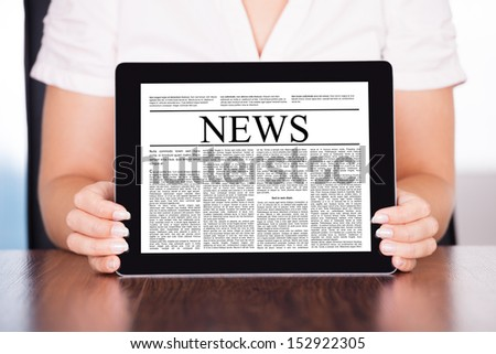 Close-up Of Woman Holding Touch Screen Tablet Pc With Business Article