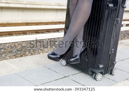 close-up of woman in high heels sitting on suitcase at train station - stock photo