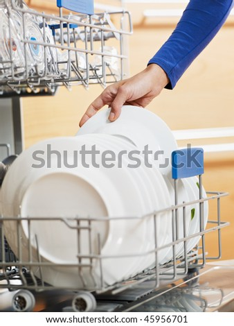 close up of woman in kitchen using dishwasher - stock photo