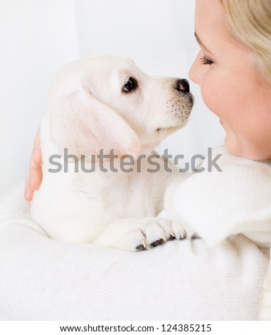 Close up of woman in white sweater embracing white puppy - stock photo
