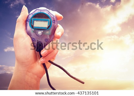 Close up of woman is holding a stopwatch on a white background against cloudy sky
