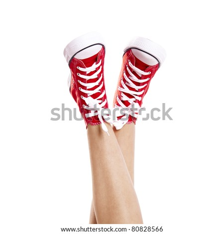 Close up of woman legs wearing a pair of red sneakers, isolated on white - stock photo