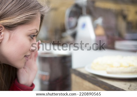 Close-up of woman looking at cake in cafe - stock photo