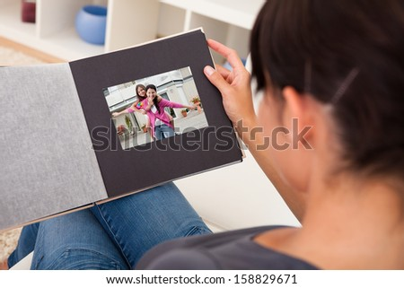 Close-up Of Woman Looking Through Photo Album; Indoors - stock photo