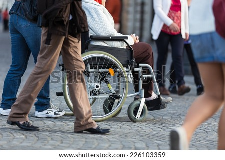 Close up of  woman on a wheelchair with a helper during walk in the busy street. - stock photo