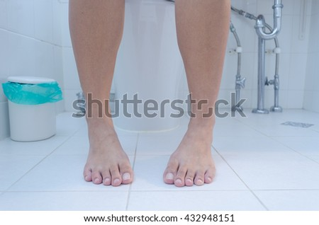 Close up of woman on toilet in morning, Color Filter - stock photo