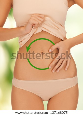 close up of woman placing hand on her belly - stock photo