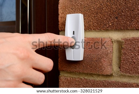 Close-up of woman pressing the button of a doorbell on a brick wall - stock photo