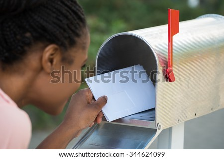 Close-up Of Woman Putting Letter In Mailbox - stock photo