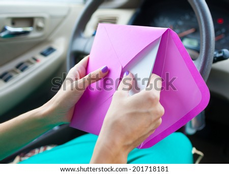 Close up of woman putting letter into envelope. - stock photo