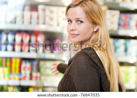 Close-up of woman reaching for products arranged in refrigerator and looking at camera - stock photo