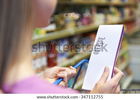 Close Up Of Woman Reading Shopping List In Supermarket - stock photo