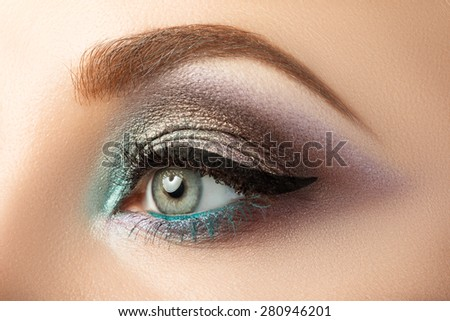 Close-up of woman's eye with creative modern make-up. Smoky eyes and arrow. - stock photo