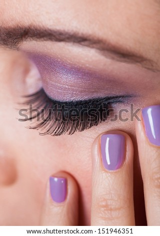 Close-up Of Woman's Eye With Purple Eyeshadow And Finger Nail Varnish - stock photo