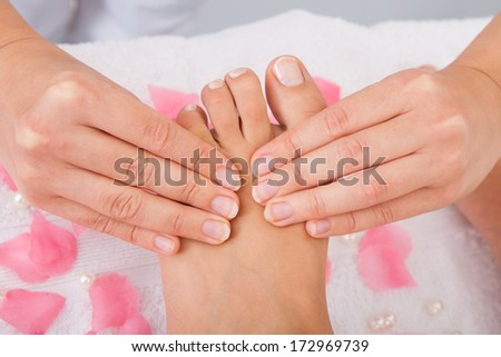 Close-up Of Woman's Feet Receiving Foot Massage In Spa - stock photo