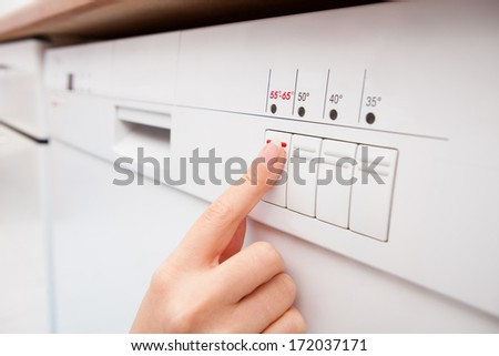 Close-up Of Woman's Finger Pressing Button Of Dishwasher - stock photo