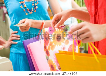 Close-up of woman?s hand holding credit card and bags with another female near by during shopping in the mall - stock photo