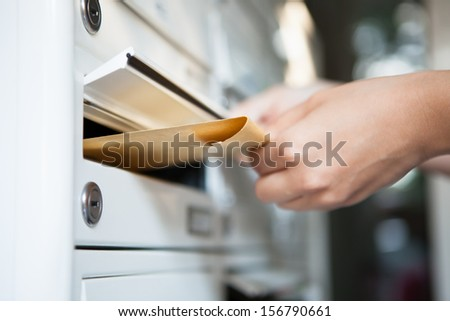 Close-up of woman's hand holding envelope and inserting in mailbox - stock photo